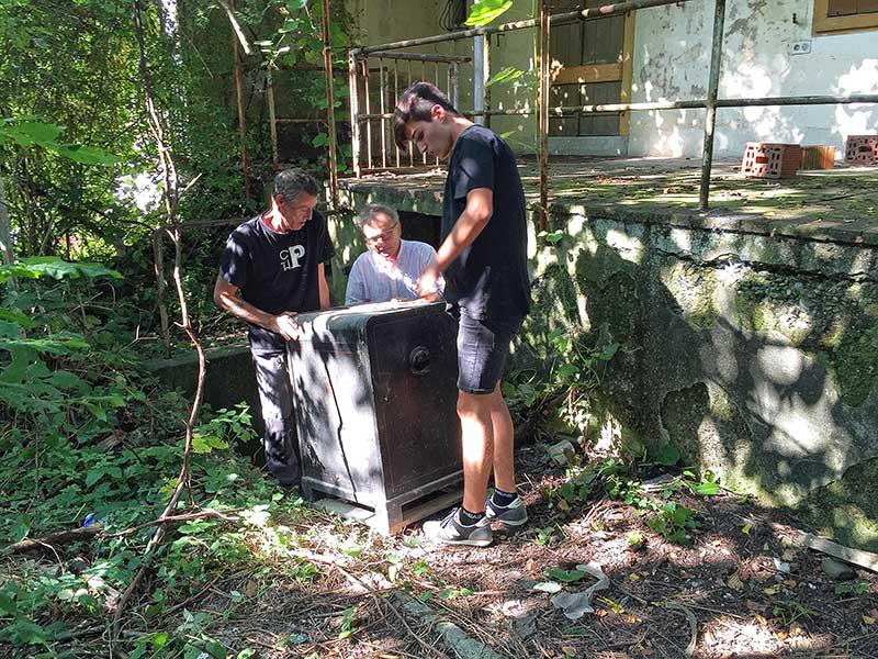 Bild: Mitarbeiter der Papiermühle transportieren die antike Druckmaschine